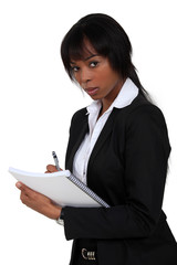 Businesswoman writing on clip-board