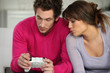 Young man and young woman playing video games