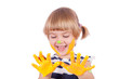 Small girl with yellow paint on her palms