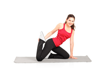 A young female athlete exercising on a mat