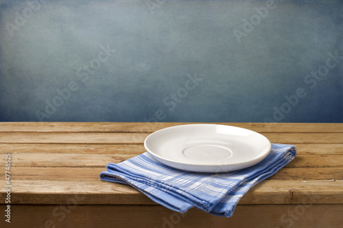 Empty plate on tablecloth on wooden table - 47748525