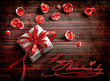 Card with holiday gift and petals from flowers on wooden table