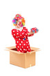 Smiling clown in a cardboard box holding a gift