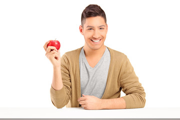 Handsome smiling guy holding a red apple and posing on a table