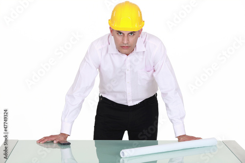architect with determined gaze and arms resting on glass table