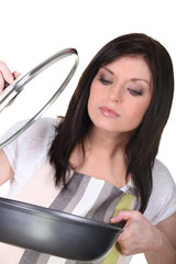 Woman lifting the glass lid on a saucepan