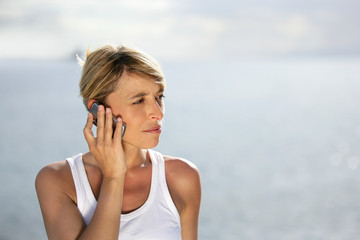 Blond woman making at call at the coast