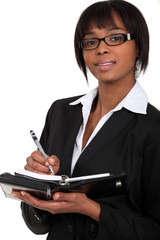 A businesswoman taking notes on a planner.