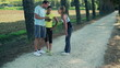 Young women with personal trainer talking in the park, crane sho