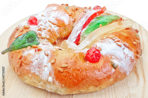Portuguese king cake on a wooden stand. On a white background. C