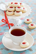 Cup of hot tea and homemade almond cookies filled with jam