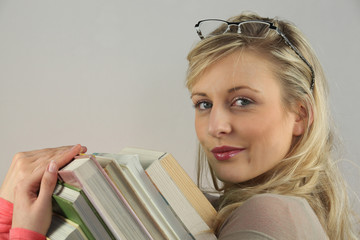 Young woman carrying a pile of books