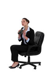 Businesswoman sat with binoculars