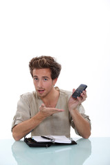 Young man with a personal organizer and cellphone