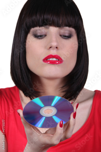 brunette woman looking a cd