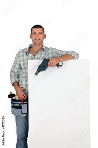 Builder with power drill stood by blank poster