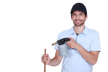 young handsome plumber at work with copper pipe and tool