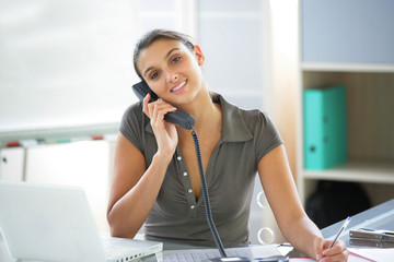 Young woman on the phone at her desk