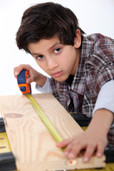 Young boy measuring a plank of wood