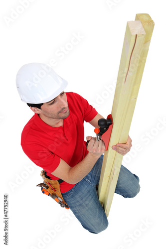 Carpenter planing wood