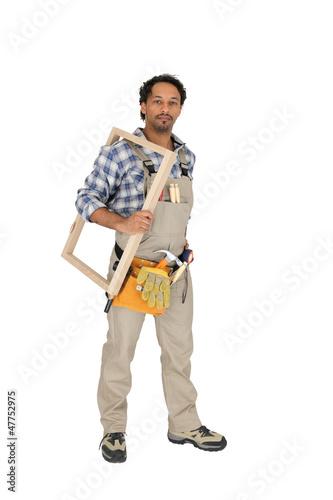 carpenter holding a window frame
