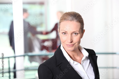 Blonde woman in front of rail