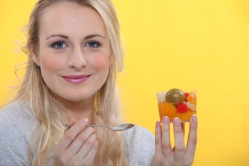 Blond woman holding fruit salad