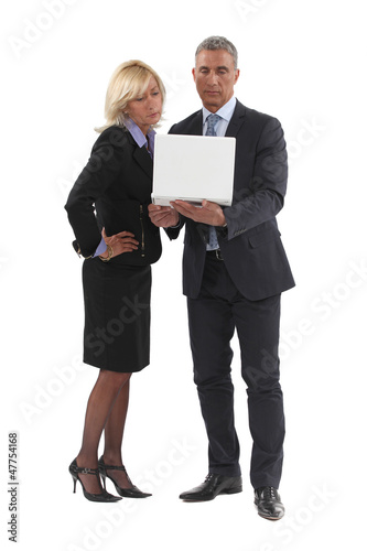 Senior business couple stood with laptop