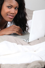 African woman with laptop in bed