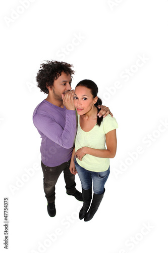Man whispering secret to young woman