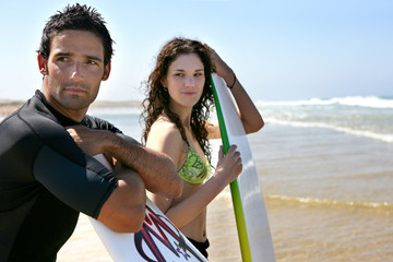 Couple stood on beach ready to surf