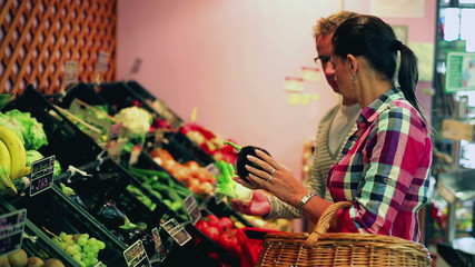 Young couple doing shopping in the greengrocer, steadycam shot