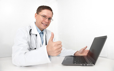Doctor with laptop sitting in doctor's office