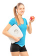 Smiling female athlete holding a weight scale and apple