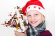 Mädchen mit Weihnachtsmütze hält Pfefferkuchenhaus