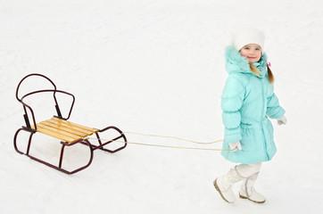 Little girl pulling her sledge in winter day