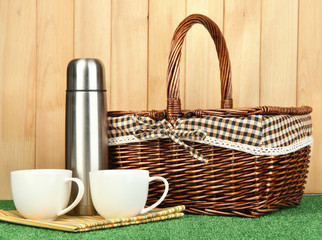 metal thermos with cups and basket on grass on wooden