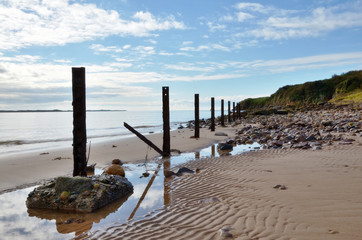 Sandy beach with a line of posts.