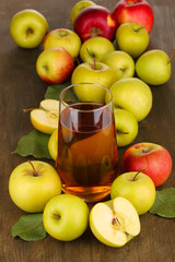 Useful apple juice with apples around on wooden table
