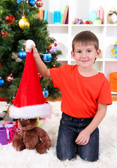 Little boy in Santa hat sits near Christmas tree
