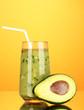 Useful fresh avocado and half avocado on orange background