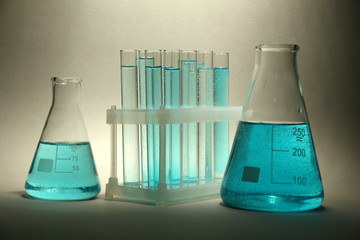 test-tubes with blue liquid on grey background