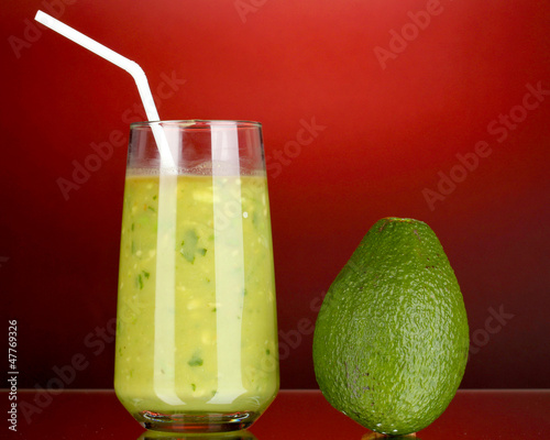 Useful fresh avocado on dark red background