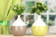 Decorative flowers in vases on windowsill