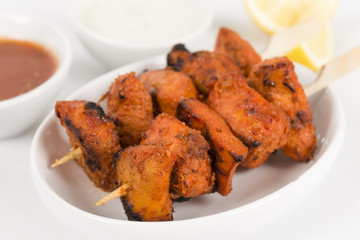 Chicken Tikka Kebab - Chicken skewers, lime wedges and dips