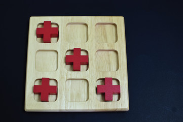 Red cross on wood board on black background