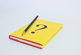 Question book with pencil on white background