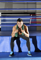 Young athlete sits on edge of ring with green towel