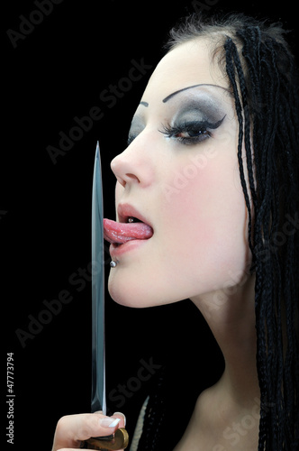 young stylish woman with dreadlocks, licking a dagger