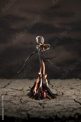 Scarecrow in the desert burning on bonfire